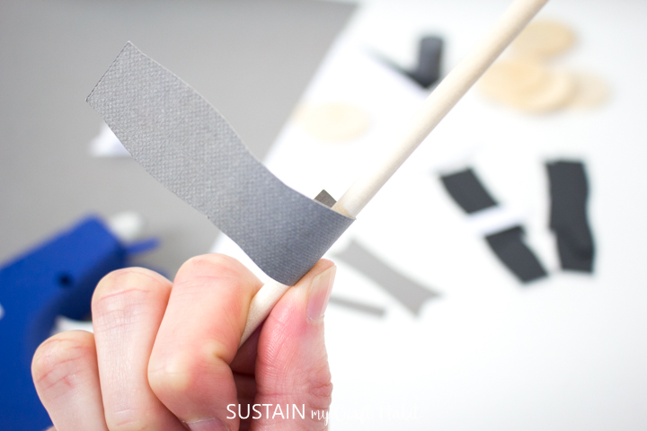 Curling the edges of the paper bow with a wooden dowel.