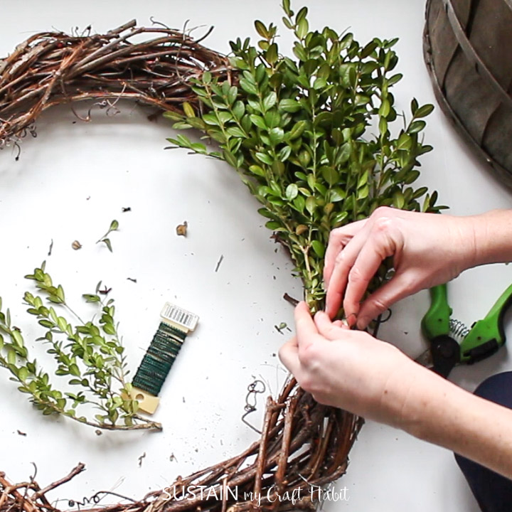 Securing bunches of boxwood against the grapevine wreath.