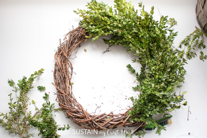 Securing bunches of boxwood together on the grapevine wreath.