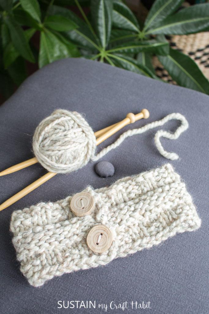 Knitted headband next to yarn and knitting needles.