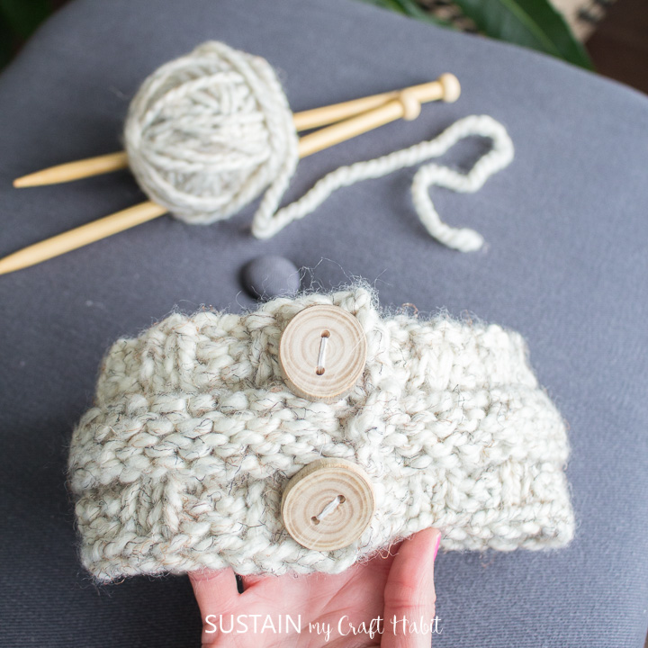 Holding a knitted headband next to yarn and knitting needles.