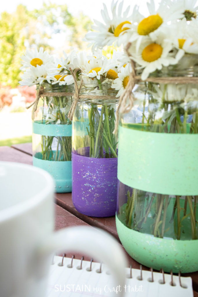 Close up of mason jar summer table centerpieces with daisies.