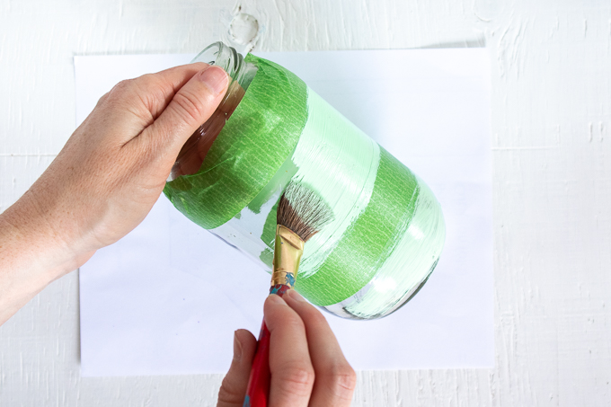 Painting the middle and bottom of a mason jar with green jade paint.