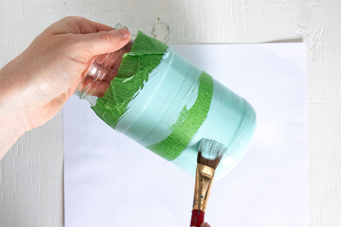 Painting the middle and bottom of a mason jar with coastal blue paint.