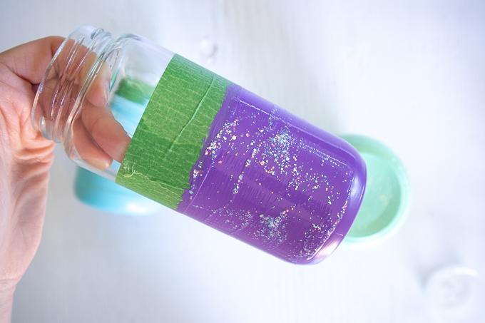 Adding glitter paint to the purple painted mason jar.