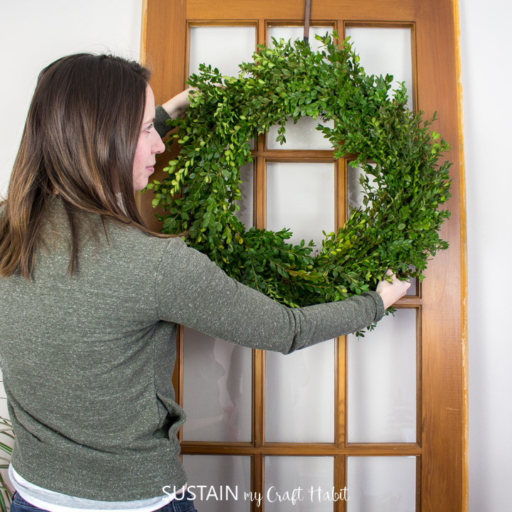 A woman hanging a boxwood wreath on a wooden door.