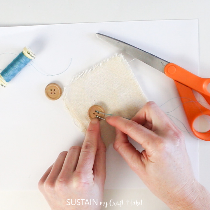 Sewing a button onto canvas fabric.