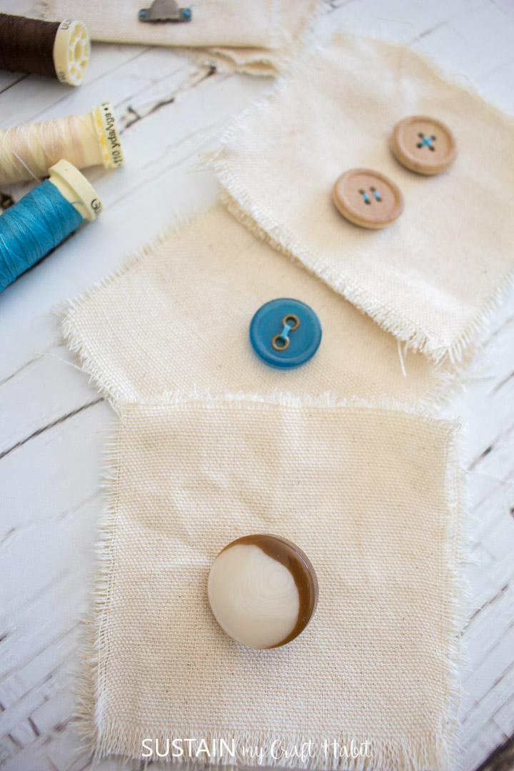 Different shaped buttons sewn to canvas fabric squares next to thread.