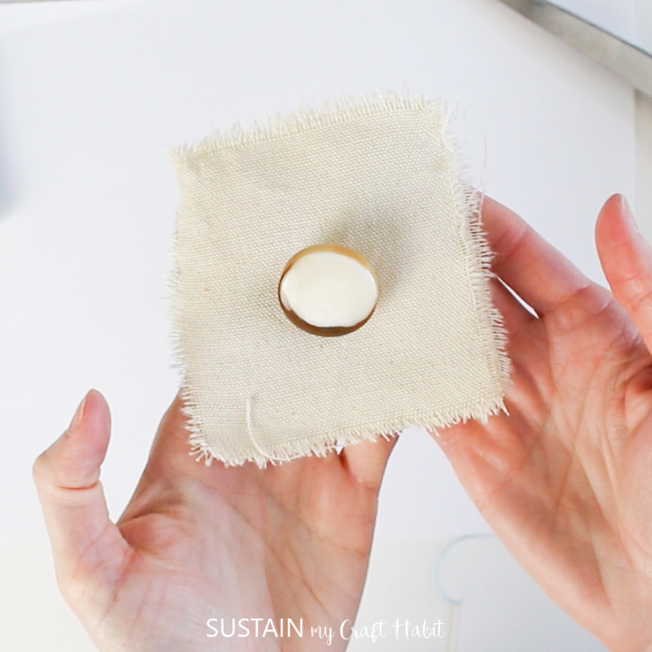 Hands holding up a sewn shank button on square fabric.