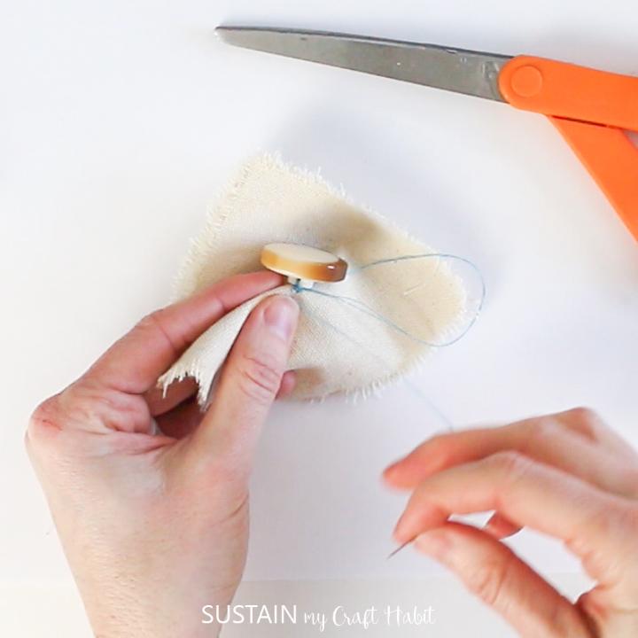 Threading a needle through a shank button and fabric.