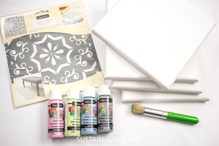 Materials needed to make Mediterranean tile stencil art including paint, paint brushes, canvas boards and a stencil.