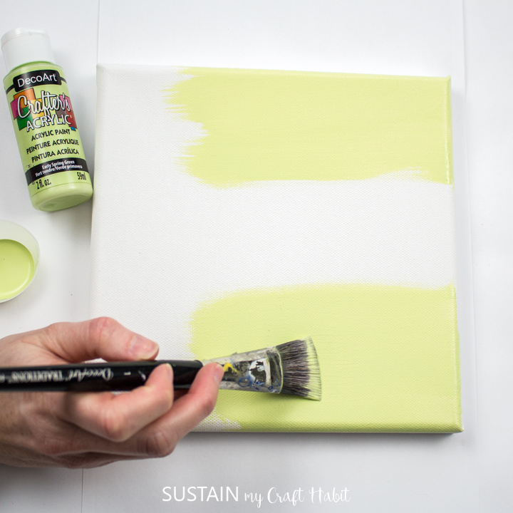 Painting a canvas with yellow paint.