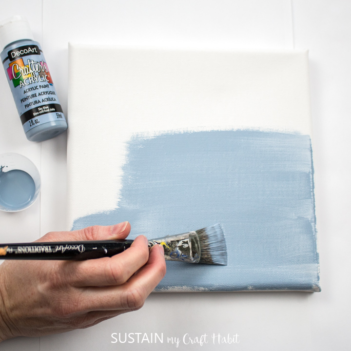 Painting a canvas with blue paint.