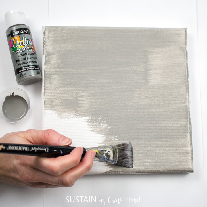 Painting a canvas with grey paint.