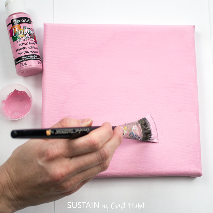 Painting a canvas with pink paint.