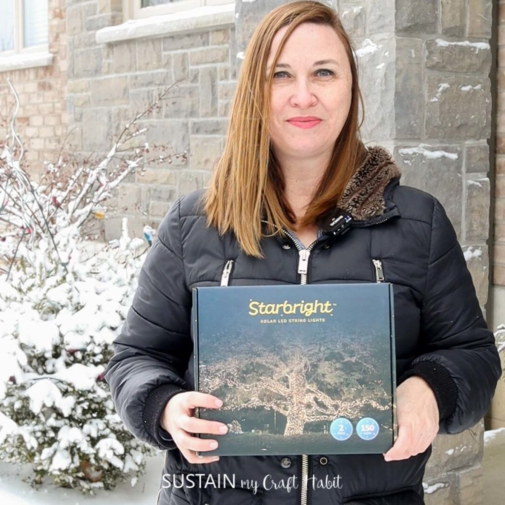 woman holding a box of Starbright Solar LED String Lights