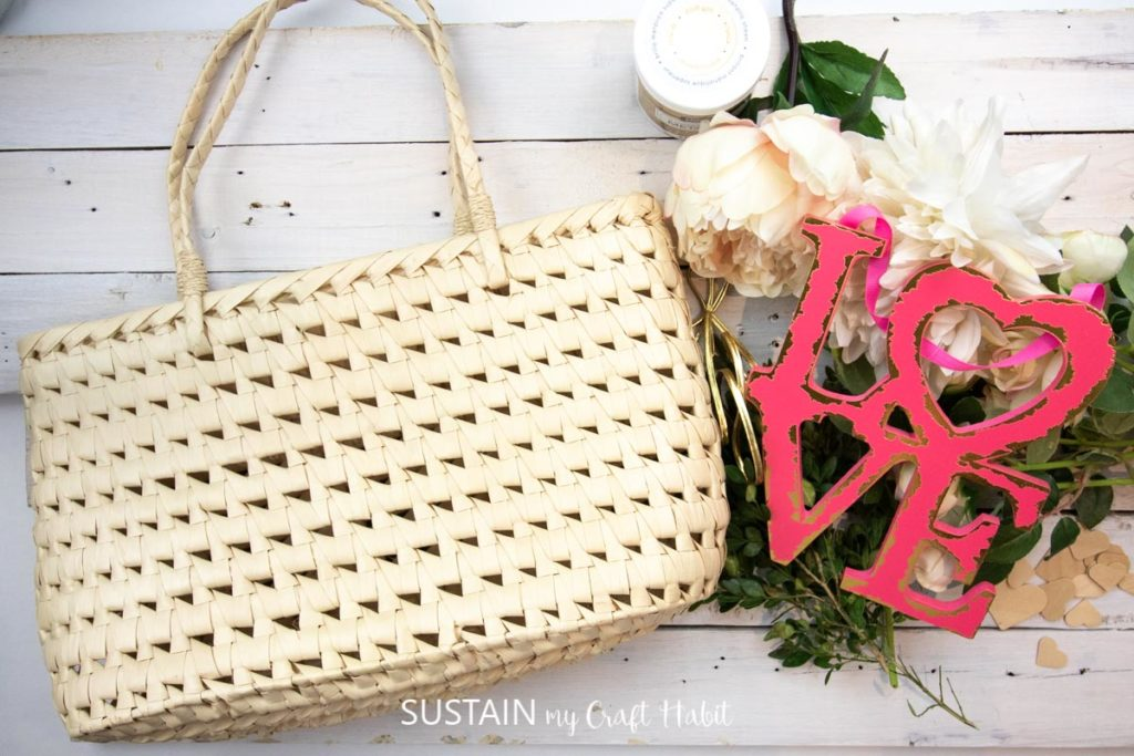 Materials needed to make a Valentine's decor, including a straw purse, love sign, flowers, greenery and wood hearts.