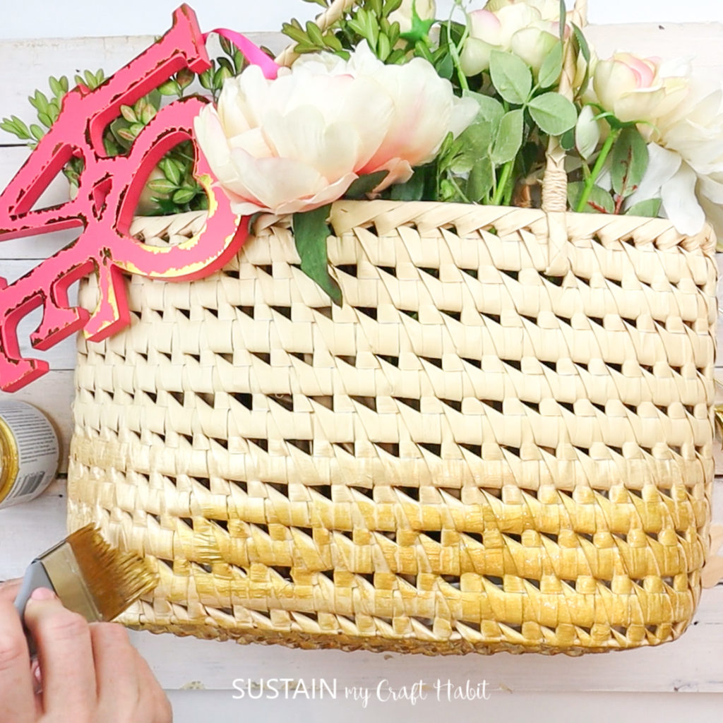 Painting the bottom of the straw purse with gold paint.