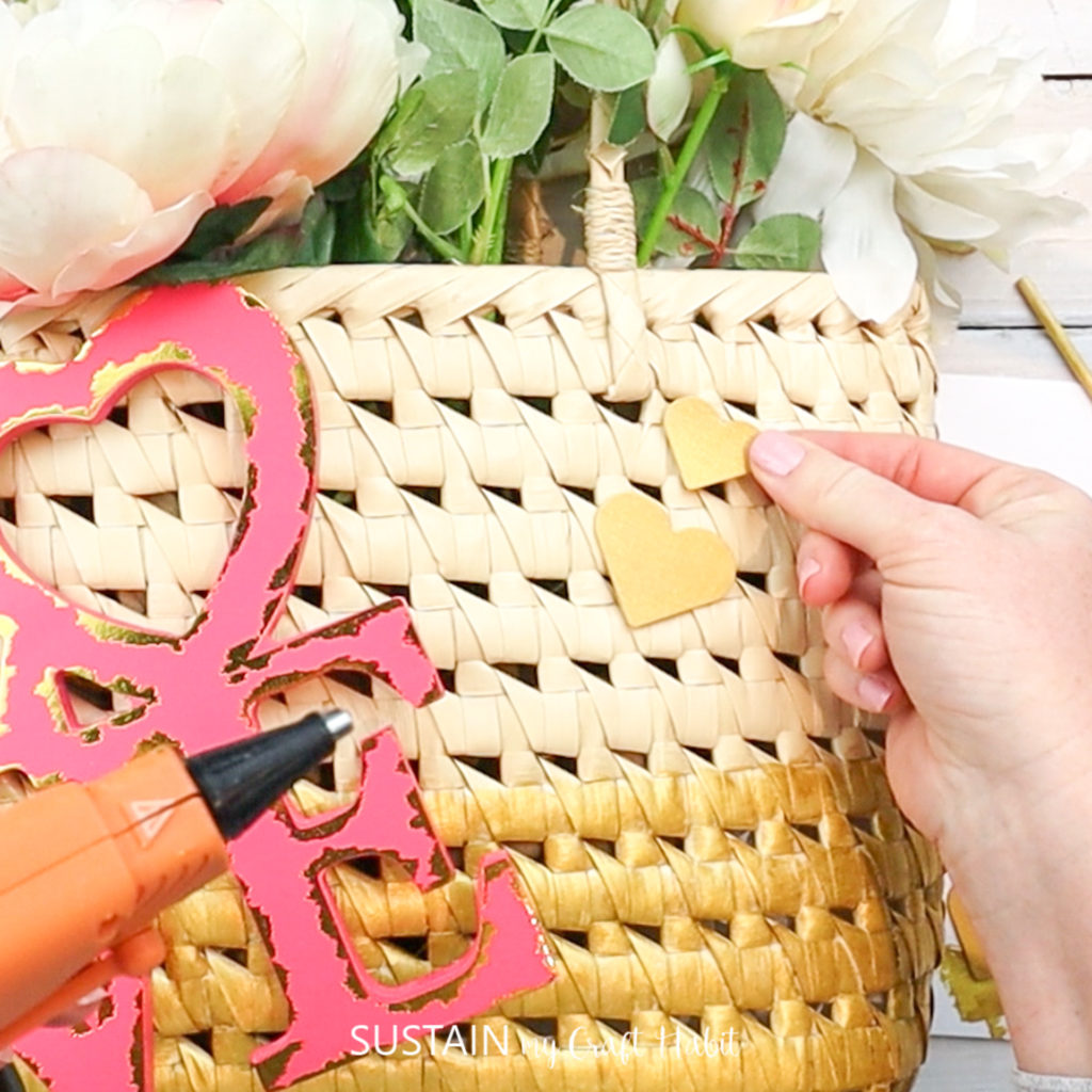 Gluing gold painted heart cutouts to the upcycled straw purse.