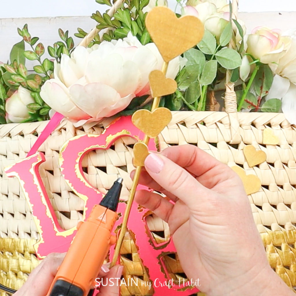 Gluing wood hearts to a wooden dowel.