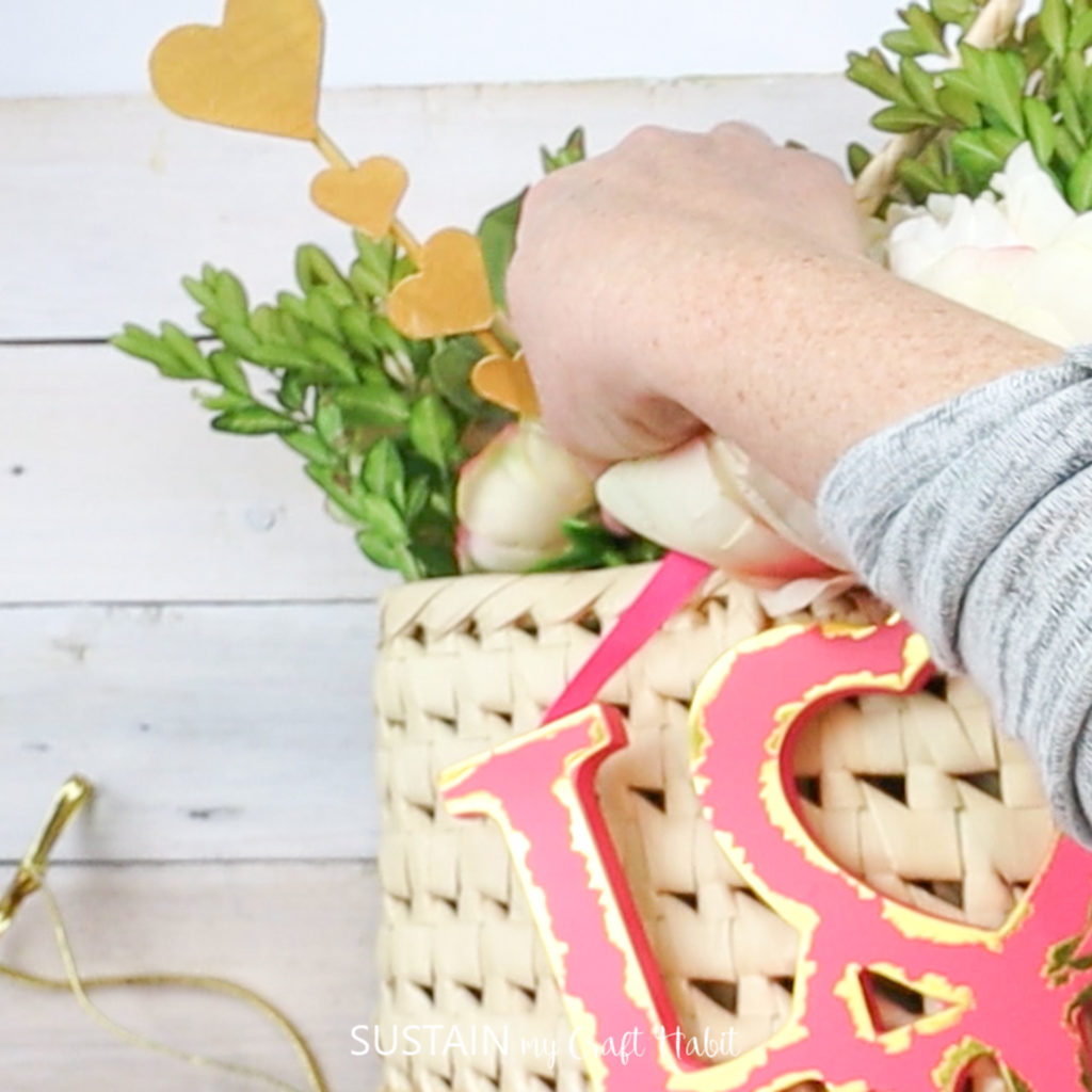 Inserting the wooden dowel with hearts into the Valentine's decor.