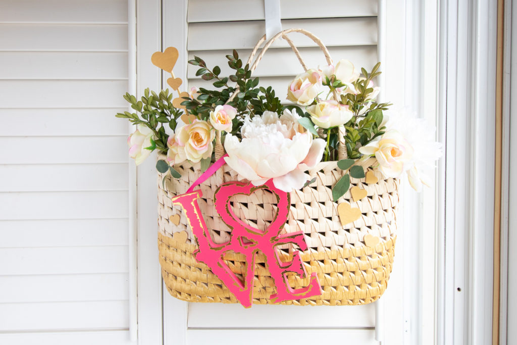 Upcycled straw purse Valentine decor that has been painted, filled with flowers and greenery and attached love sign.