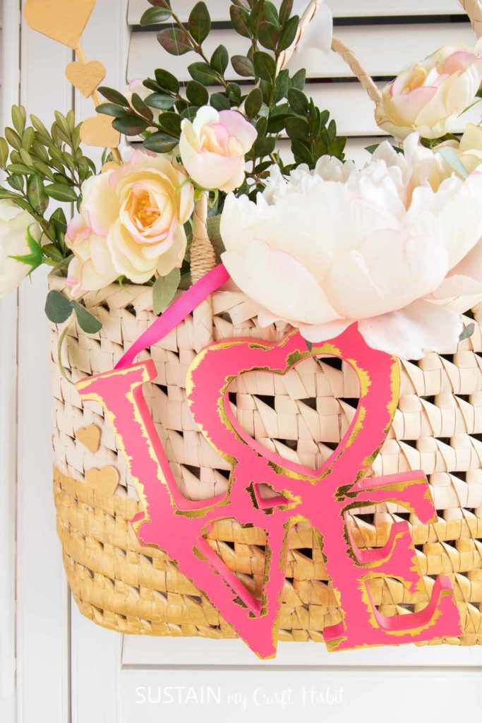 Close up of the wood love sign attached to the upcycled straw purse Valentine's decor.