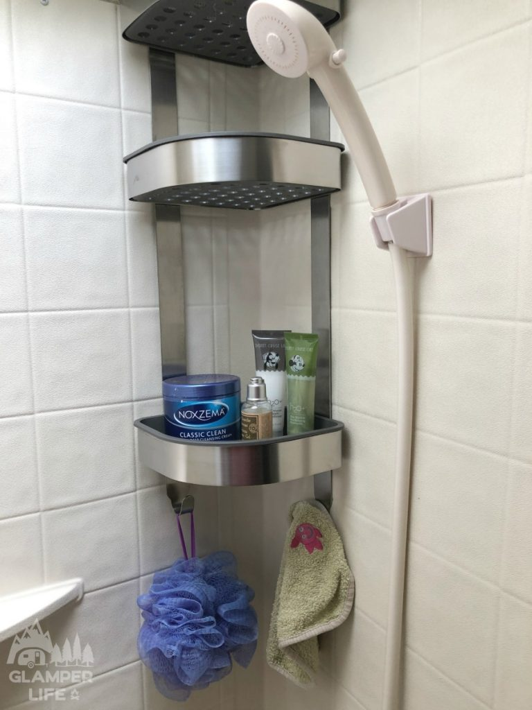 Silver shower caddy with toiletries.