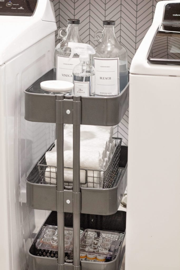 Silver cart holding laundry supplies.