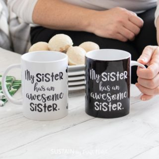 Matching black and white mugs on a white would surface table. A stack of desert plates with cookies are in the background.