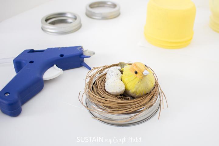 Gluing a decorative nest with bird onto a mason jar lid.