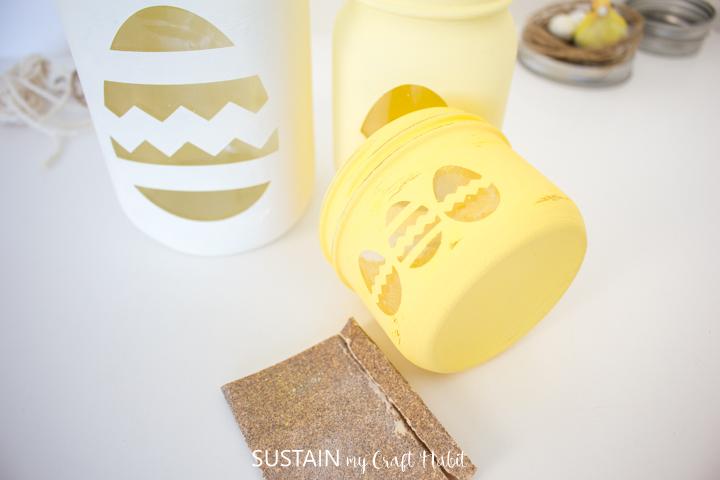 Using sandpaper to distress the painted mason jars.