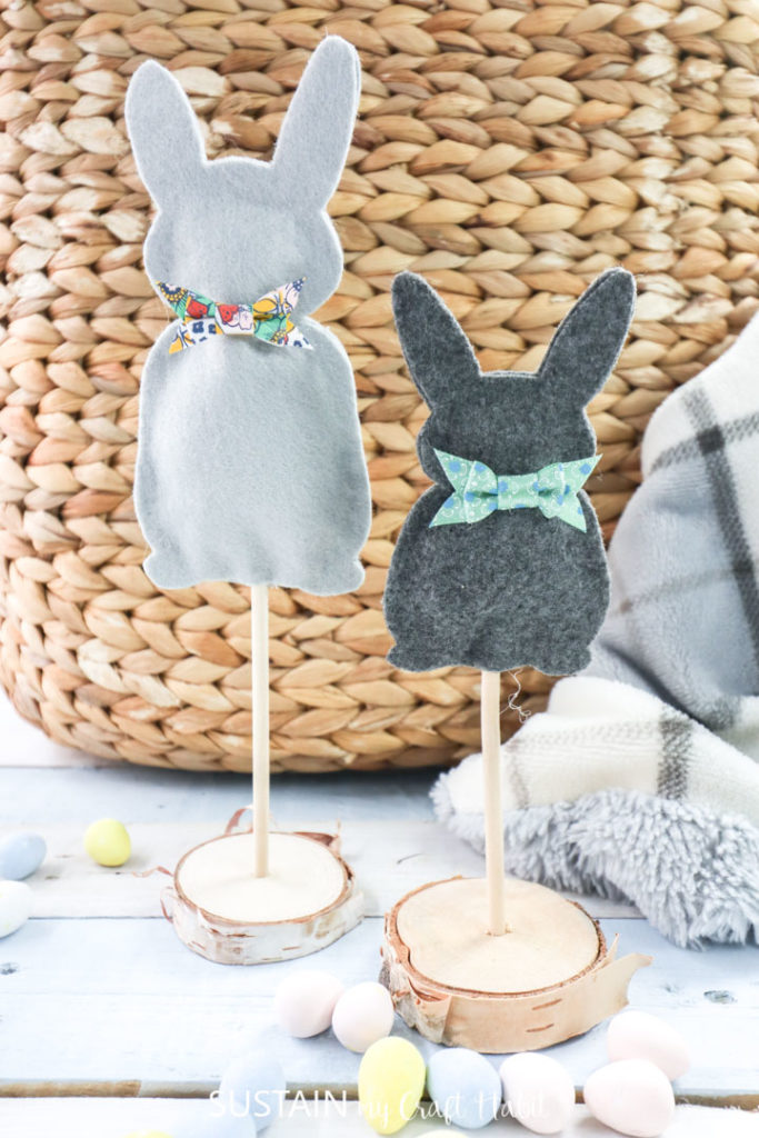 Felt bunnies standing on wooden dowels and birch wood with candy scattered around the bunnies.