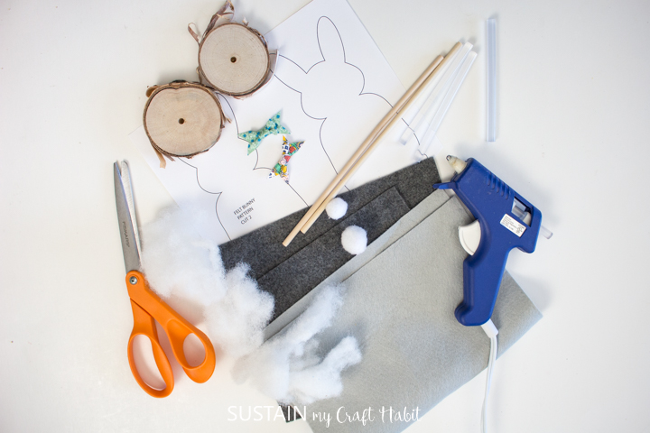 Materials needed to make felt bunny Easter decor including felt fabric, a template, wooden dowels, birch wood slices, scissors and hot glue.