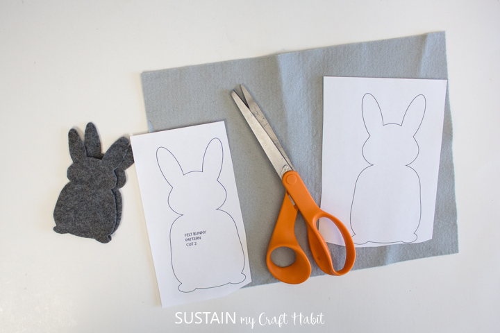 Setting the bunny templates on felt fabric with scissors.