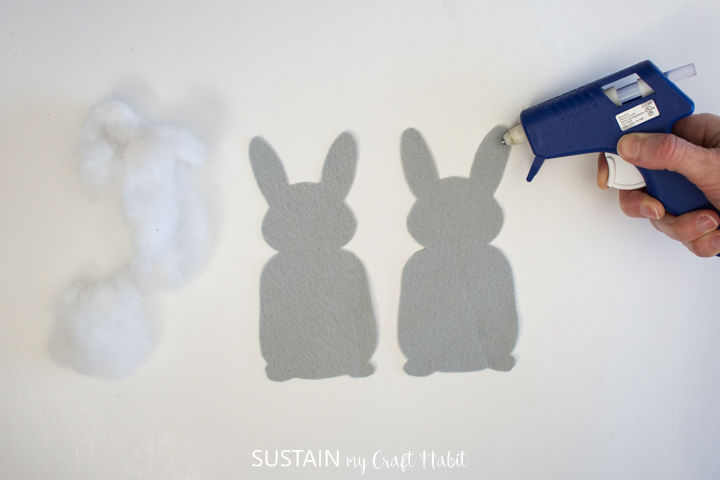 Adding hot glue to a felt bunny ear.
