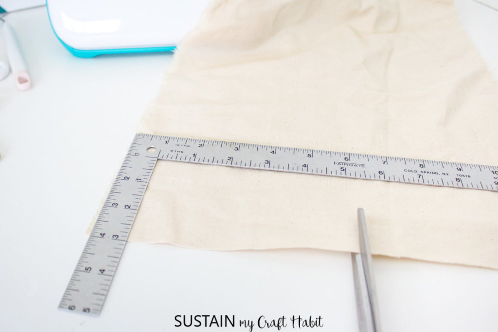 Cutting a piece of cotton fabric with scissors.