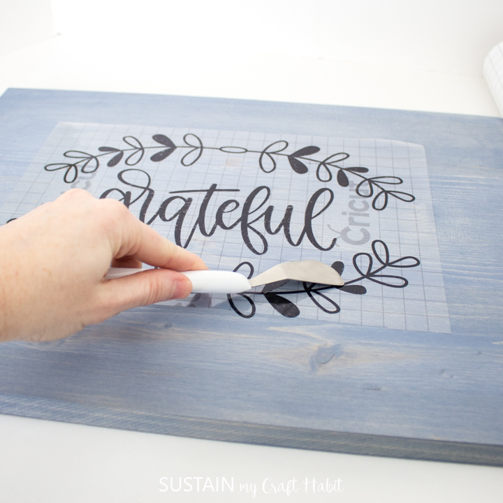 Using a Cricut scraper tool to rub the vinyl cut out onto the painted wood piece.