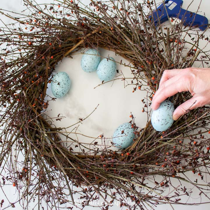 Gluing an Easter egg to the twig wreath.