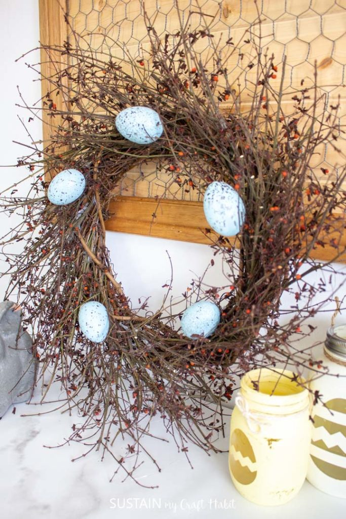 Rustic birds nest twig wreath with decorative Easter eggs.