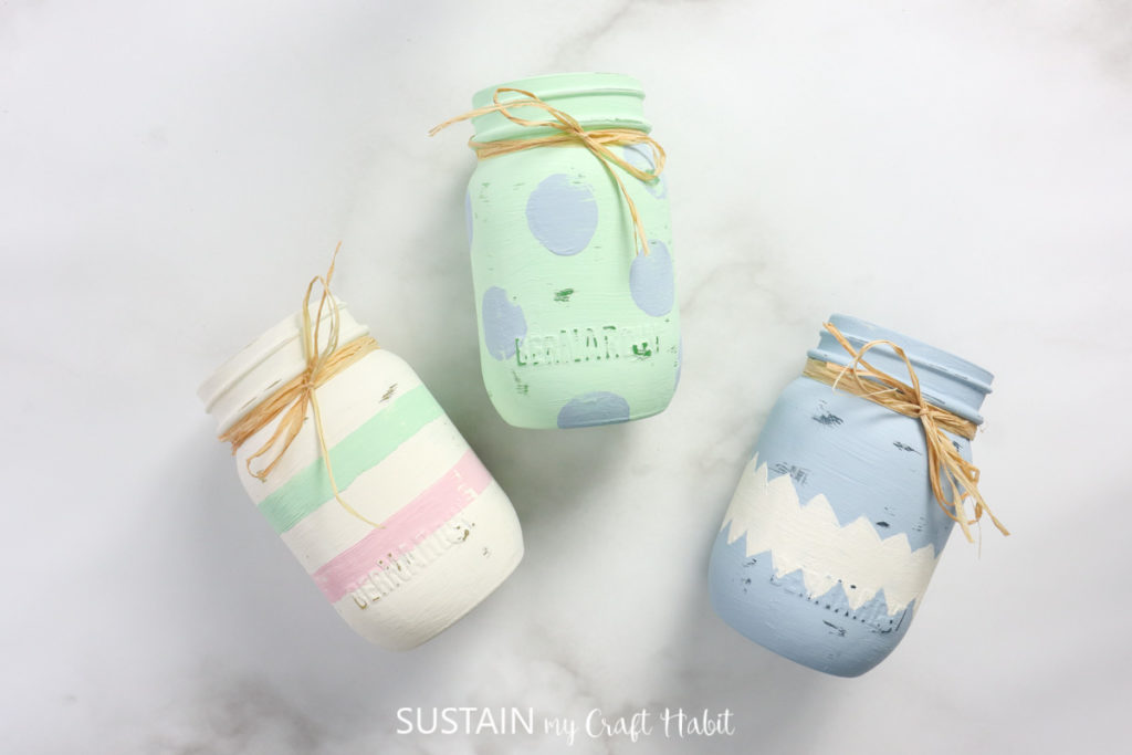 Three painted Easter jars wrapped in ribbon.