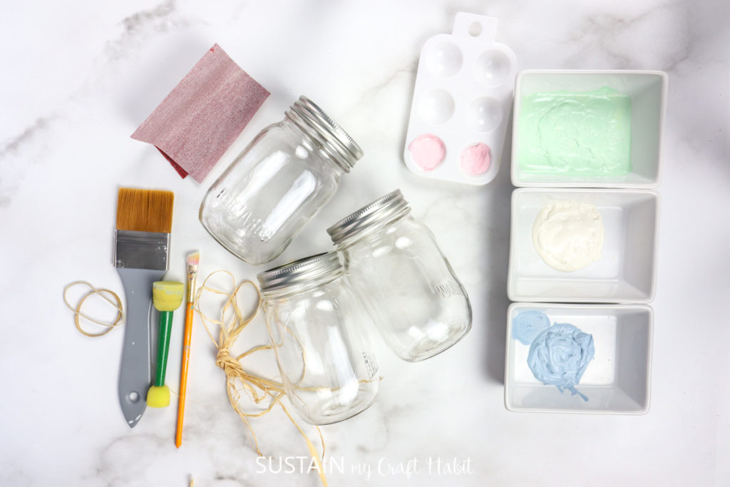 Materials needed to make decorative painted Easter jars including mason jars, paint, paintbrushes, rubber band and sandpaper.