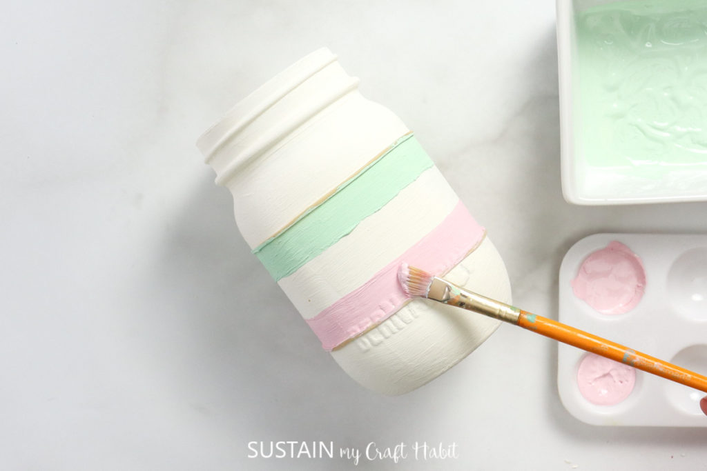 Painting green and pink lines next to the rubber bands.
