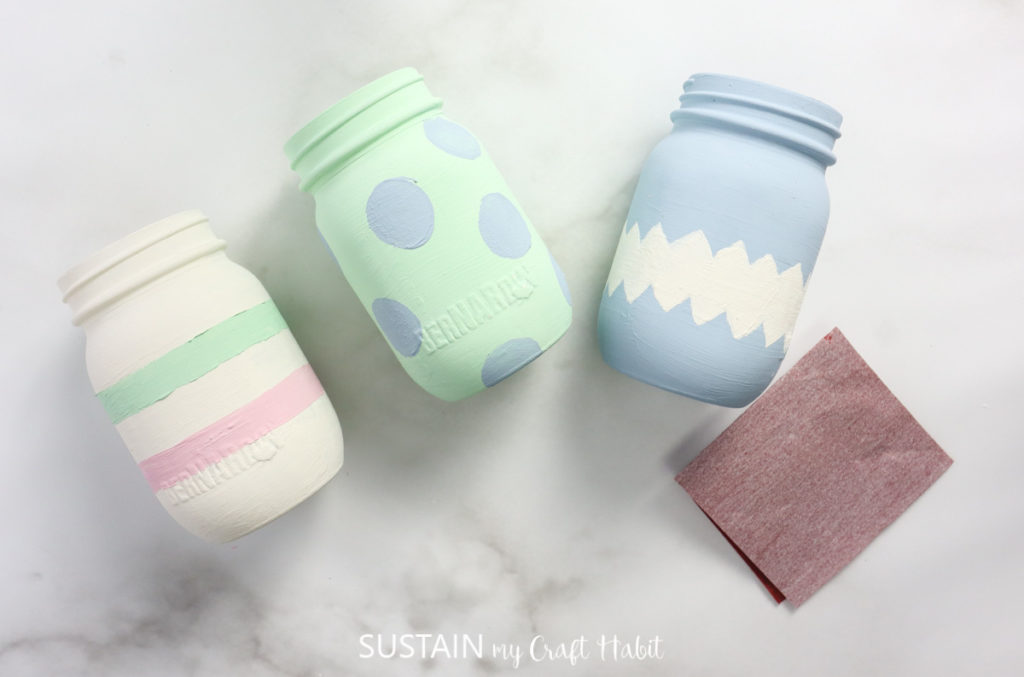 Painted Easter jars next to a piece of sandpaper.