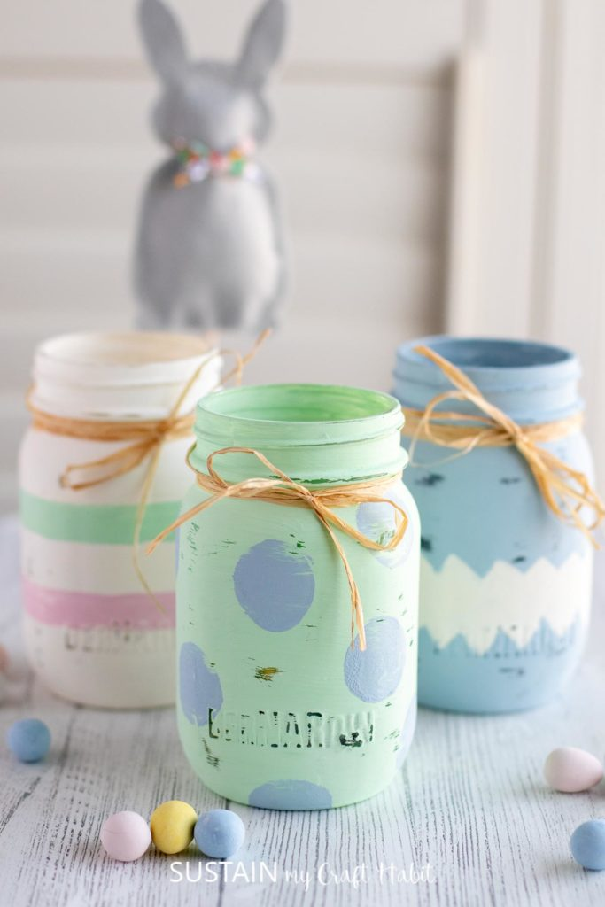 Three painted Easter jars wrapped in ribbon with chocolate eggs scattered around.