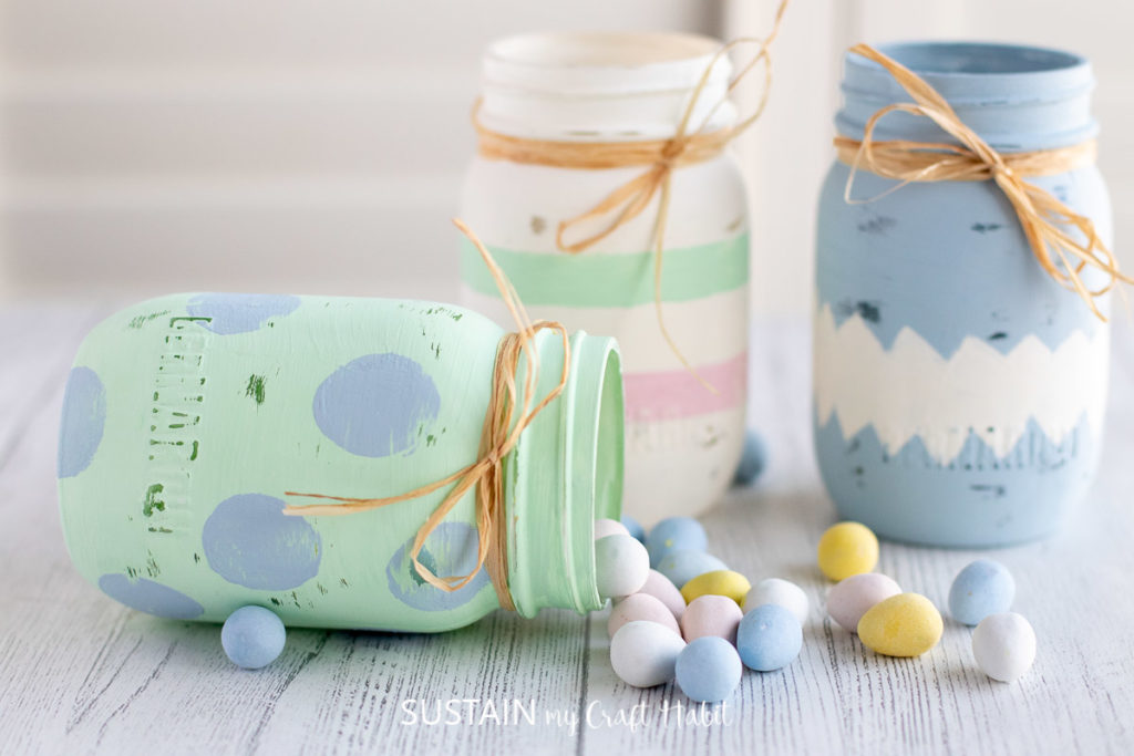 Three painted Easter jars wrapped in ribbon, one jar is laying on it's side with chocolate eggs spilling out.