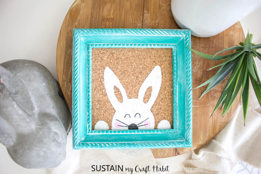 Overhead view of a painted Easter bunny in a blue frame.