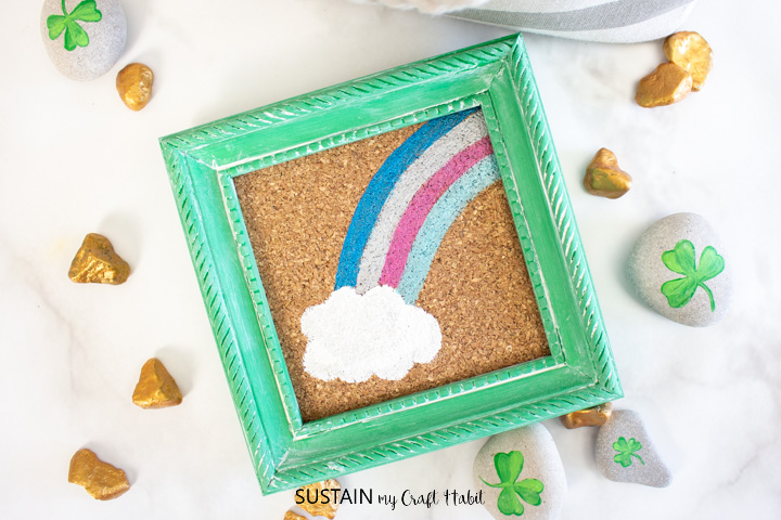 Framed St. Patrick's day craft next to painted rocks.