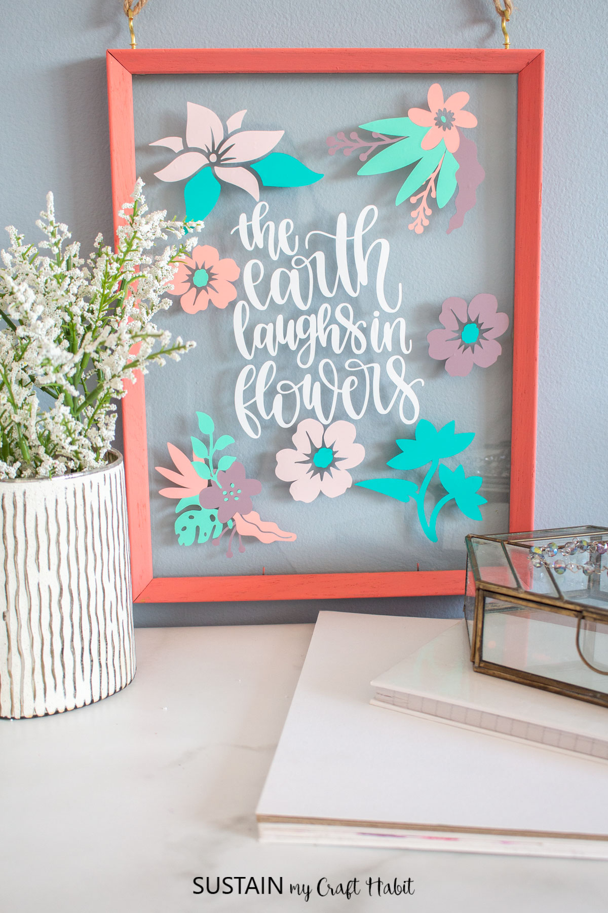 "Completed spring wall art with the phrase ""the earth laughs in flowers"" in white vinyl with colorful vinyl flowers all around."