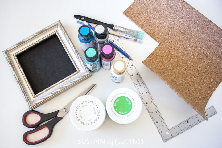 Materials needed to make a framed St. Patrick's day craft including a picture frame, cork board, paint, paintbrushes, scissors and ruler.